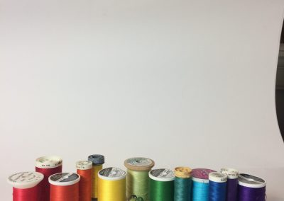 Compositon photo of sewing thread in rainbow colors and sequence